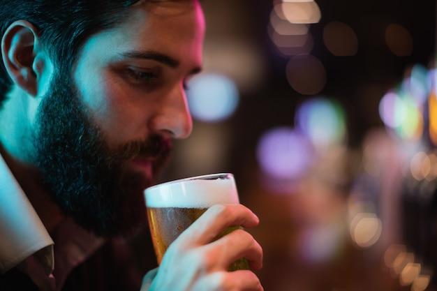 Homem tomando um copo de cerveja