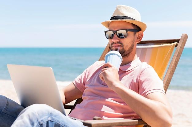 Homem tomando uma bebida na praia e trabalhando no laptop
