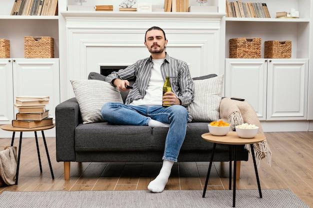 Homem tomando uma cerveja e assistindo tv dentro de casa