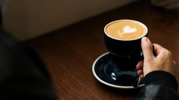 Homem tomando uma xícara de café quente em um café