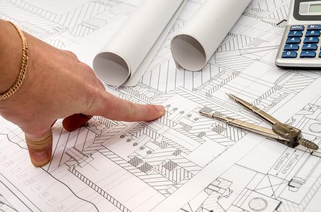 Homem trabalha com desenho técnico, peças de máquinas.