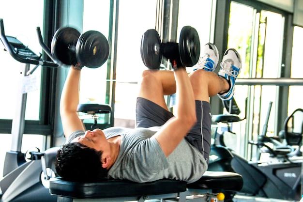 Homem trabalha com sinos de despejo em fitness