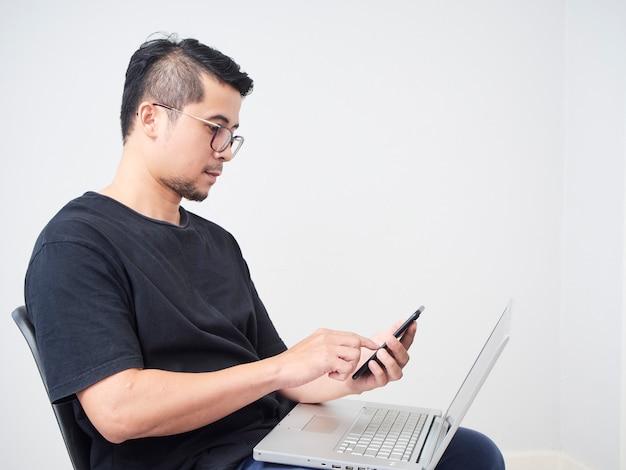 Homem trabalha com smartphone e laptop