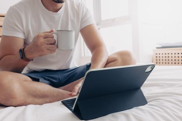 Homem trabalha com tablet e café no conceito de quarto de trabalho em casa