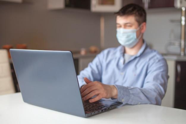 Homem trabalha em casa em um laptop