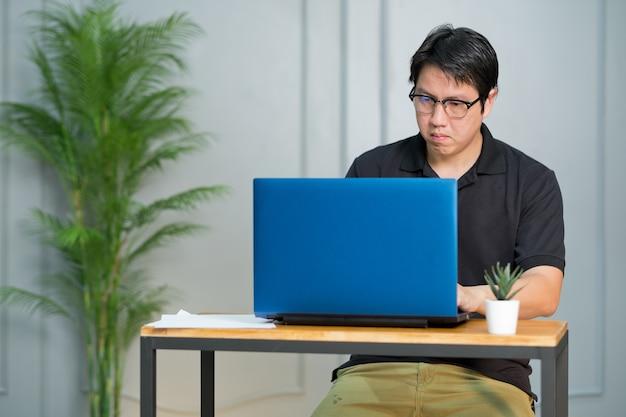 Homem trabalha em casa, usa laptop para o trabalho, fica em casa