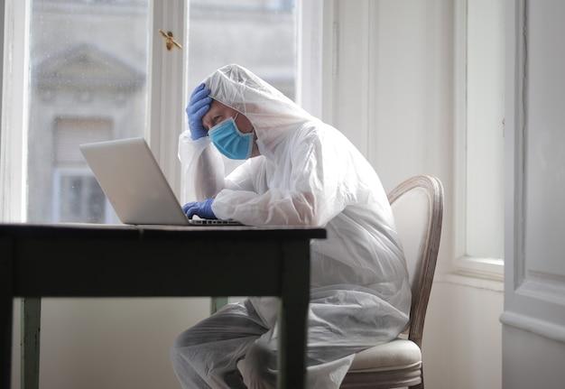 Homem trabalha em um computador protegido por um traje médico e uma máscara