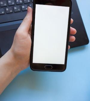 Homem trabalha em um laptop e segura um telefone na mão sem rodeios. o problema de concentração no trabalho enquanto trabalhava em casa. homem distraído com o telefone enquanto trabalhava em casa no laptop.