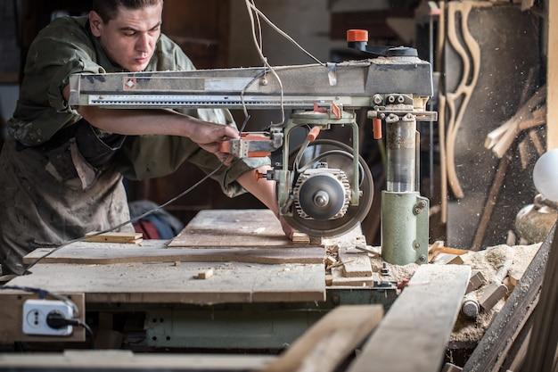 Homem trabalha na máquina com o produto de madeira