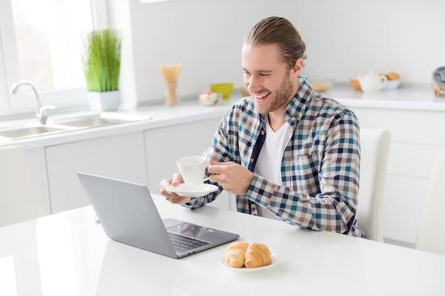 Homem trabalha no laptop e bebe café
