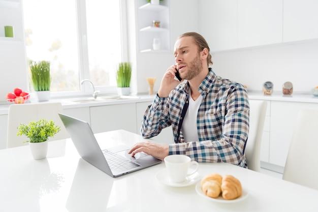 Homem trabalha no laptop e fala no telefone