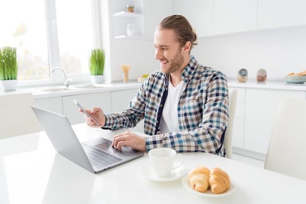 Homem trabalha no laptop e usando o telefone