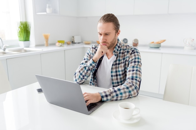 Homem trabalha no laptop na cozinha
