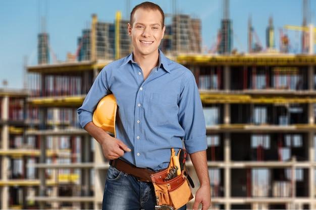 Homem trabalhador bonito com cinto de ferramentas no fundo