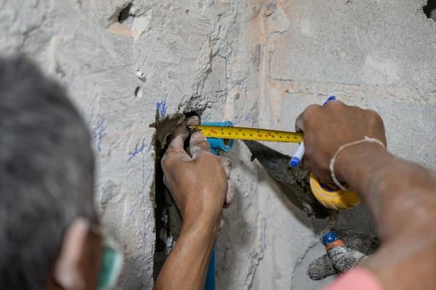Homem trabalhador com fita métrica medindo cano de água na parede de concreto para reformar banheiro