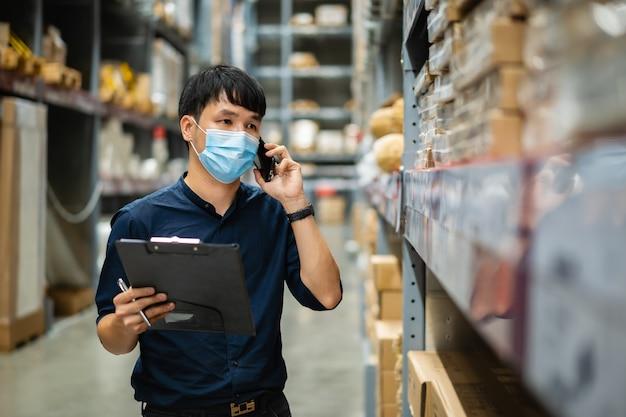 Homem trabalhador com máscara médica falando em um telefone celular e segurando a prancheta para verificar o estoque no armazém durante a pandemia de coronavírus