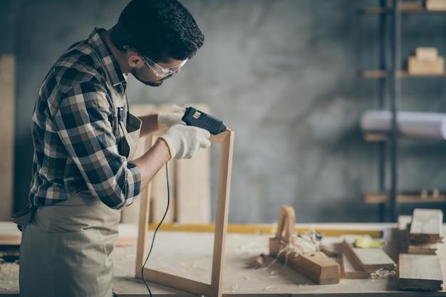 Homem trabalhador concentrado sério usa pistola elétrica de cola quente para consertar estruturas de madeira na garagem da casa