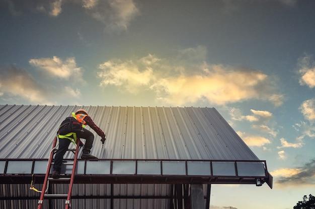 Homem trabalhador construindo comerciante no telhado de uma casa com capacete de segurança