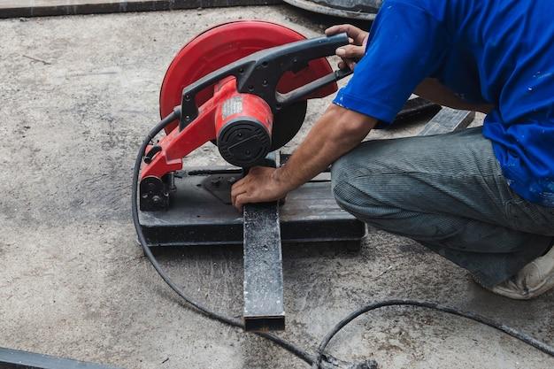 Homem trabalhador cortando aço com um cortador de aço circular.