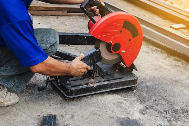 Homem trabalhador cortando aço com um cortador de aço circular. Foto Premium