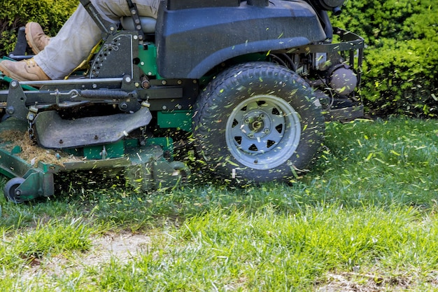 Homem trabalhador cortando grama no verão com um jardineiro profissional cortando grama