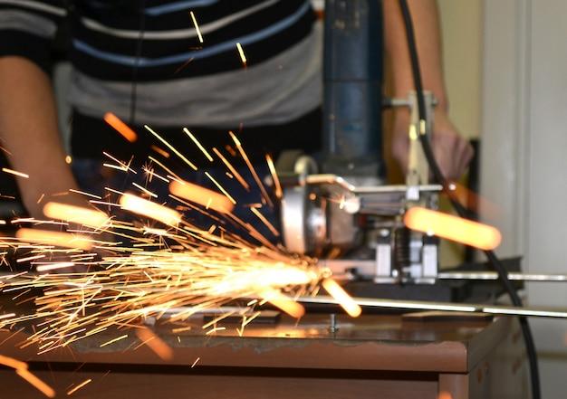 Homem trabalhador cortando um tubo de metal em duas partes e muitas faíscas voando direto para o close-up da câmera.