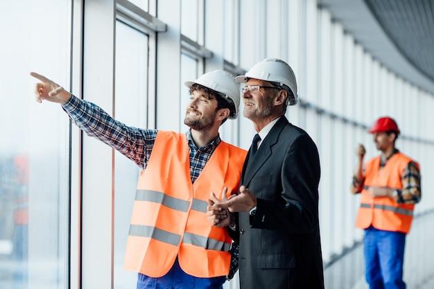 Homem trabalhador da construção civil apontando planos arquitetônicos e arquiteto