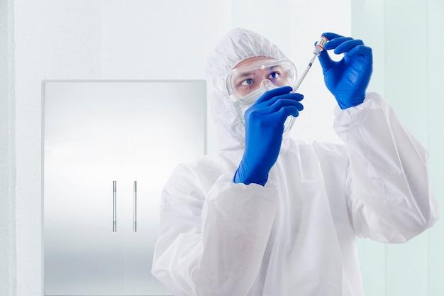 Homem trabalhador da saúde com uma roupa de proteção e luvas segurando covid 19 vacinas no hospital