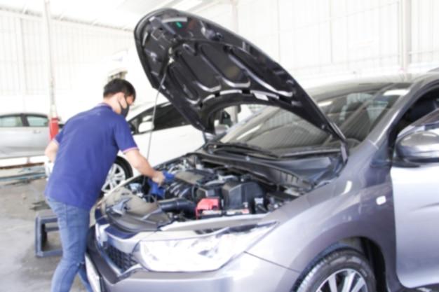 Homem trabalhador desfocado abre o capô do carro com a limpeza do capô do carro e sala de máquinas.