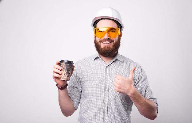 Homem trabalhador engenheiro usando capacete branco, bebendo um café para viagem e mostrando o polegar