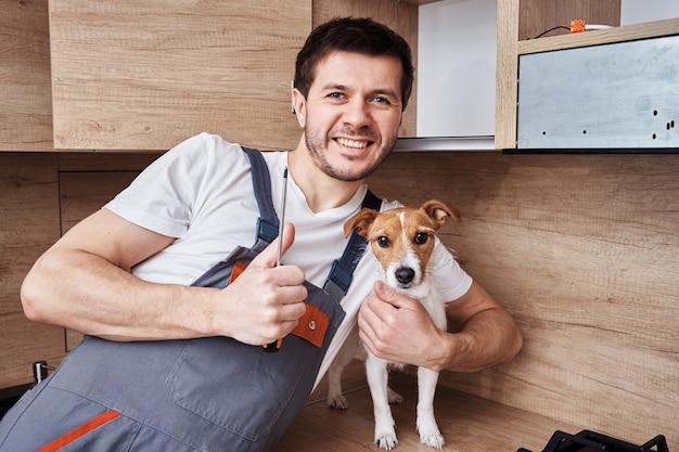 Homem trabalhador feliz de uniforme com uma chave de fenda na mão sorrindo, mostrando o gesto e abraçando o cachorro no fundo da cozinha
