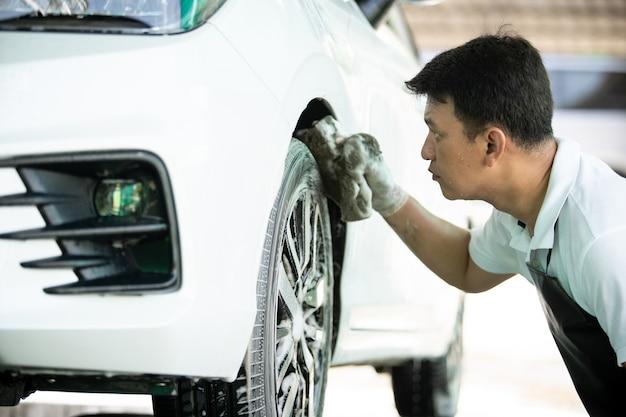 Homem trabalhador na garagem lavando um carro sujo usando um sabão lava-carros e uma escova para limpar a sujeira de um pneu