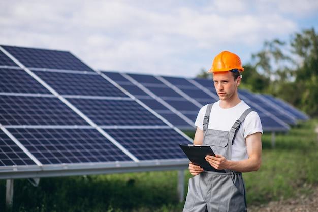 Homem trabalhador no firld pelos painéis solares