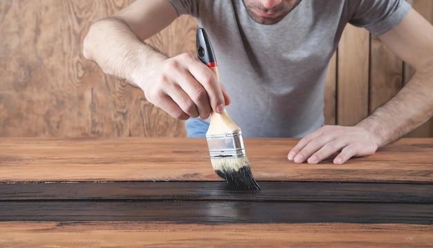 Homem trabalhador pintando madeira com um pincel pintando pranchas de madeira