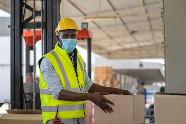 Homem trabalhador usa máscara facial com colete de segurança e capacete amarelo, preparando a entrada do produto para a caixa para envio na fábrica do armazém