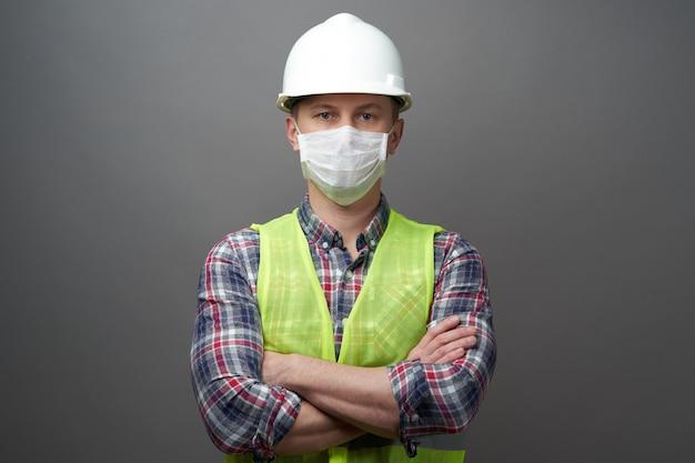 Homem trabalhador vestindo máscara higiênica e capacete protetor.