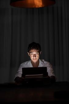 Homem trabalhando à noite, tiro médio
