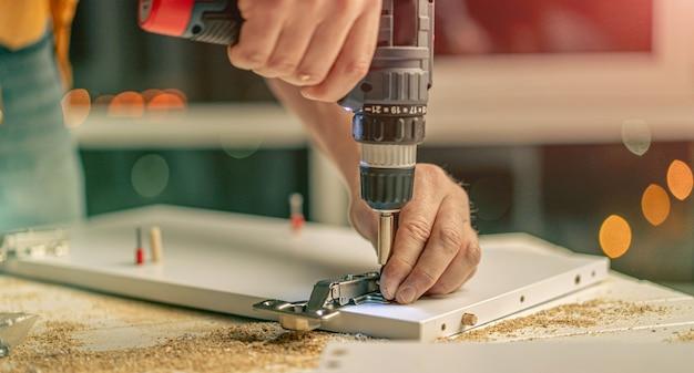 Homem trabalhando com chave de fenda elétrica e parafusos durante o processo de fabricação de móveis