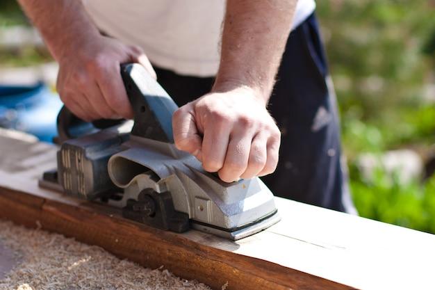 Homem trabalhando com ferramentas e tábuas de madeira
