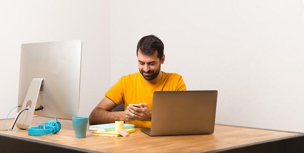 Homem, trabalhando, com, laptot, em, um, escritório, conversa móvel