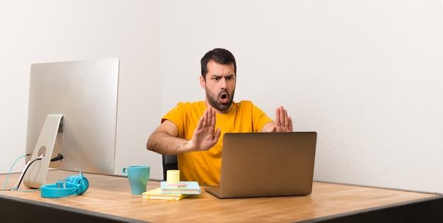Homem, trabalhando, com, laptot, em, um, escritório, fazer, parada, gesto, para, decepcionado, com, um, opinião