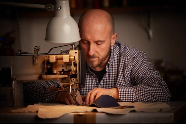 Homem trabalhando com máquina de costura, fazendo máscara facial caseira para prevenir e impedir a propagação do vírus corona