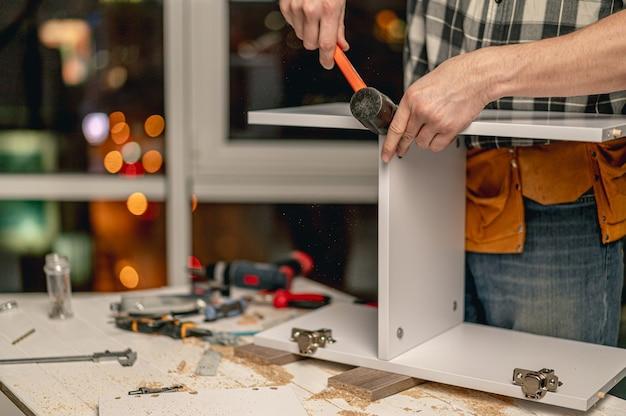 Homem trabalhando com martelo para conexão de peças durante o processo de fabricação de móveis de madeira na oficina