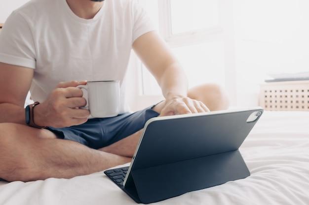 Homem trabalhando com tablet e café no quarto