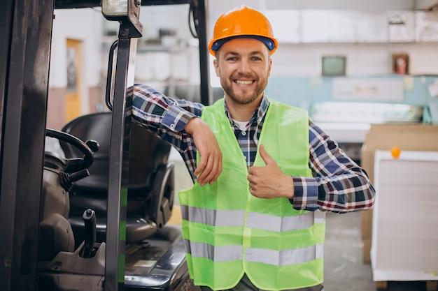 Homem trabalhando em armazém e dirigindo empilhadeira