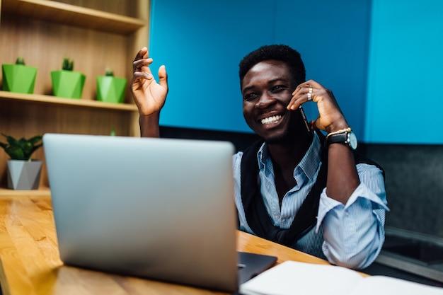 Homem trabalhando em casa com o laptop na mesa da cozinha, segurando o telefone, o conceito freelance.