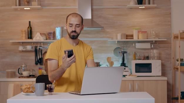 Homem trabalhando em casa com sistema de iluminação de automação, sentado na cozinha, apaga as luzes usando comando de voz para aplicativo de casa inteligente no smartphone