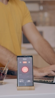 Homem trabalhando em casa com sistema de iluminação de automação usando controle de voz no smartphone, desligando ...