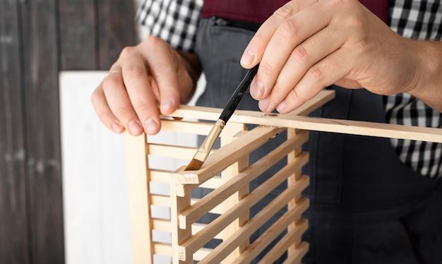 Homem trabalhando em close-up de objeto de madeira