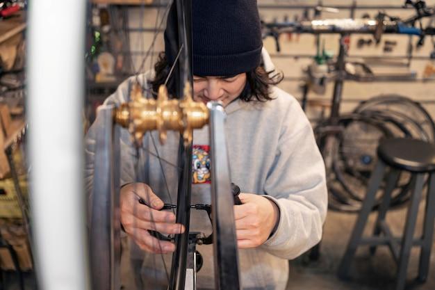 Homem trabalhando em loja de bicicletas tiro médio